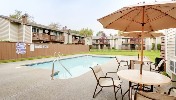 Swimming pool area with shaded seating at Arbor Chase Apartment Homes in Kent, WA
