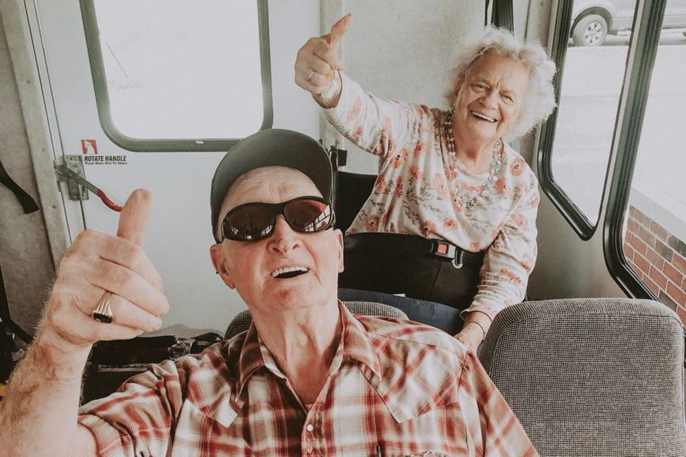 Male and female residents on a bus ride giving a thumbs up at Village Green Health Campus in Greenville, Ohio