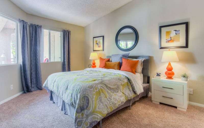 Spacious master bedroom with plush carpeting at Tuscany Village Apartments in Ontario, California