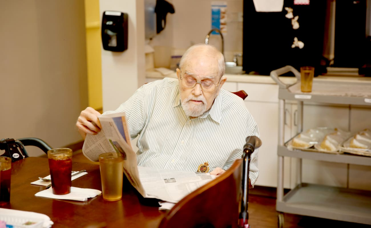 A resident reading the paper at breakfast at Providence Assisted Living in Grenada, Mississippi.