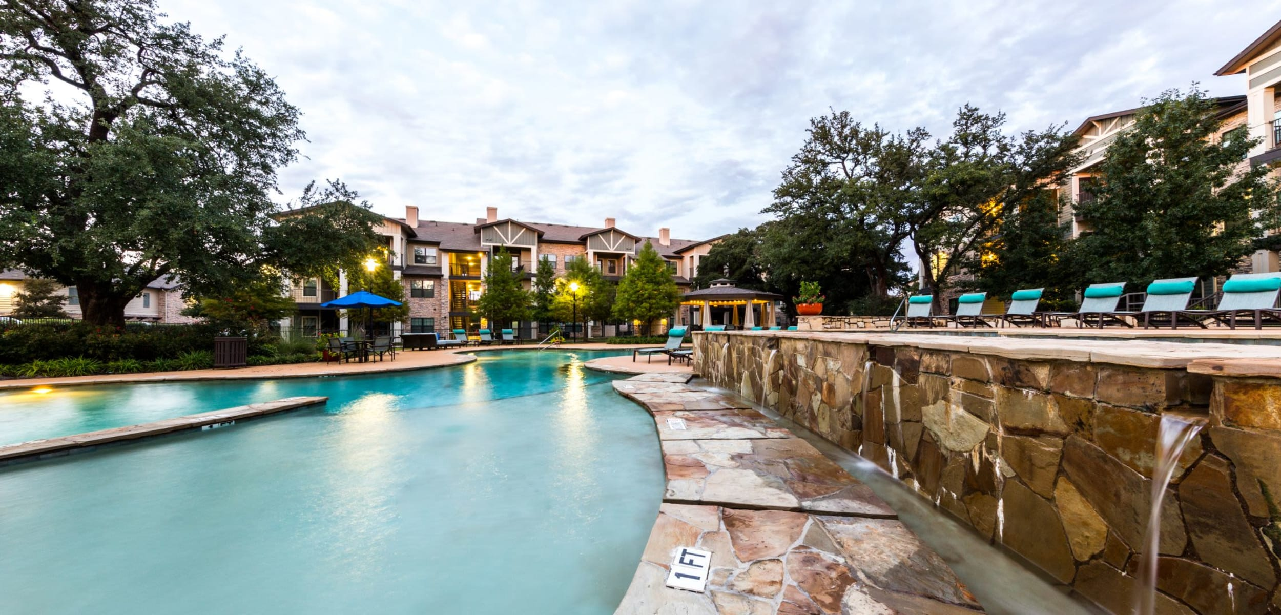 Lit pool with a water feature at Marquis on Lakeline in Cedar Park, Texas