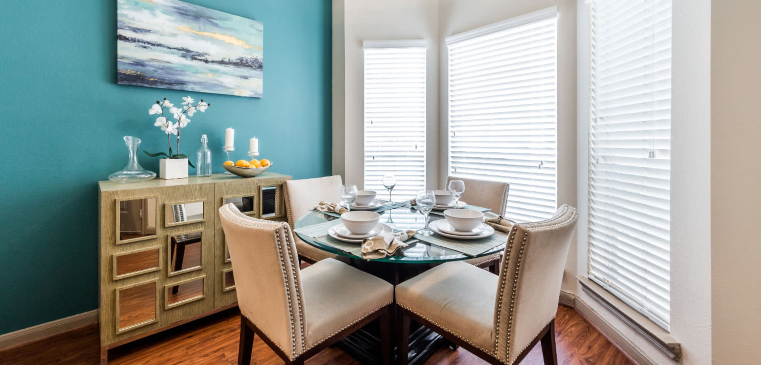 Bright dining area with multiple windows and wood flooring at Marquis on Park Row in Houston, Texas