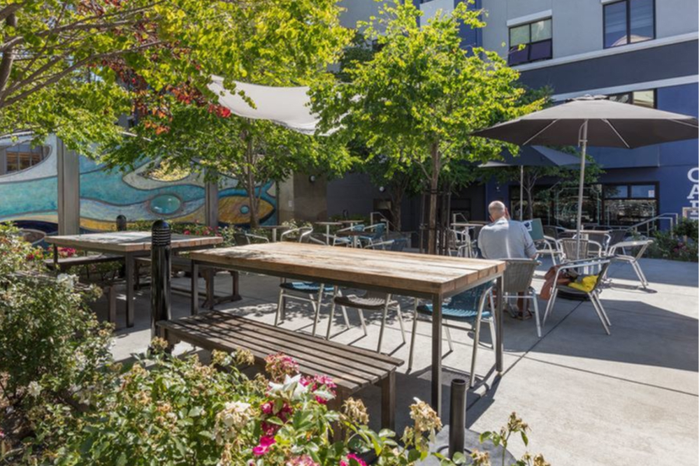Outdoor seating at the cafe on the ground floor of K Street Flats Apartment Homes in Berkeley, California