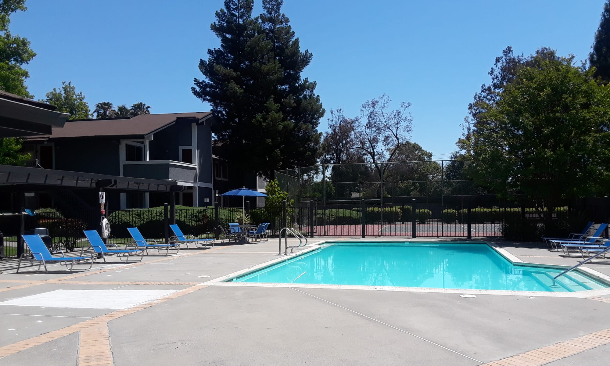 Exterior Pool shot with lounges, tennis court in background in Fairfield, CA