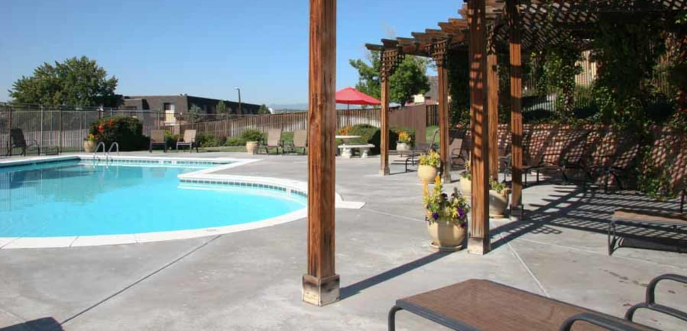 Swimming pool and shaded seating under pergola at Montair Apartment Homes in Thornton, CO