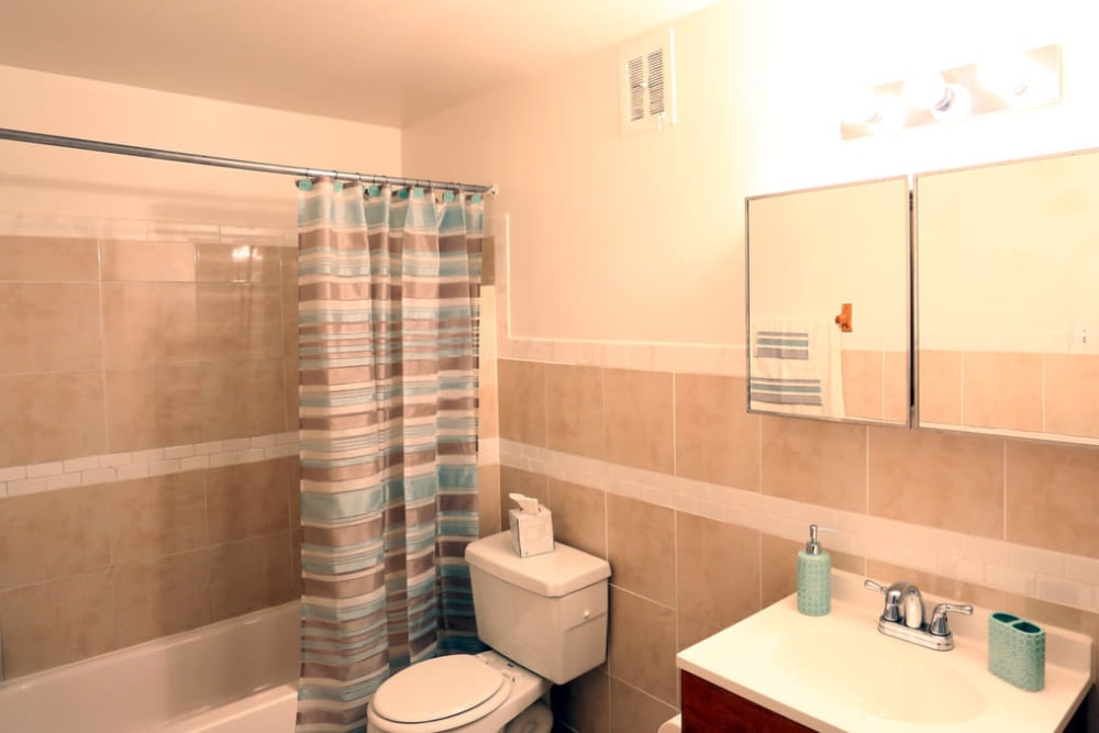 A bathroom with a large mirror at Bishop - Stratford Court Apartments in Stratford, New Jersey