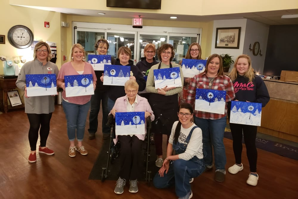 Residents with winter landscape paintings at Brookstone of Aledo in Aledo, Illinois