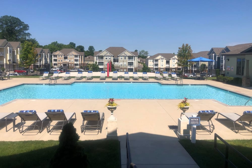 Clubhouse and resident buildings behind the swimming pool on a beautiful day at The Retreat at Arden Village Apartments in Columbia, Tennessee