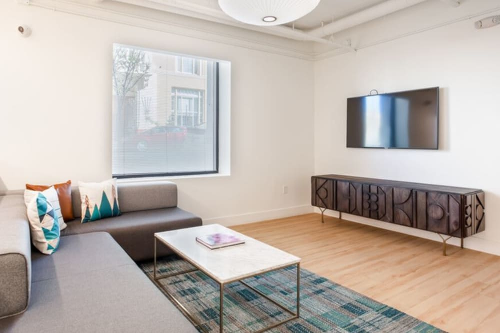 Model living area with wood-style flooring at K Street Flats Apartment Homes in Berkeley, California