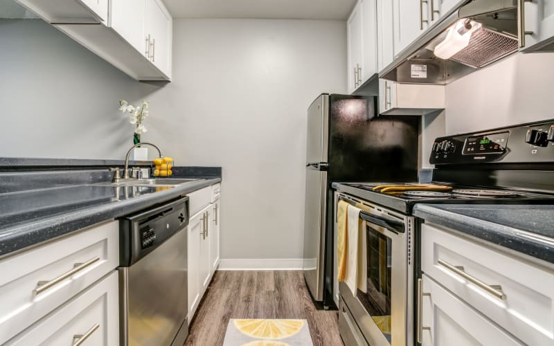 Renovated kitchen with white cabinets at The Timbers Apartments in Hayward, California