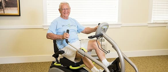 Resident on exercise bike at The Enclave at Cedar Park Senior Living in Cedar Park, Texas