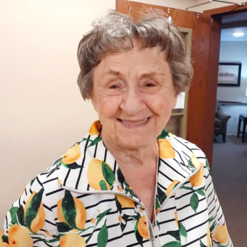 Smiling resident in a floral zip-up sweater at The Oxford Grand Assisted Living & Memory Care in McKinney, Texas