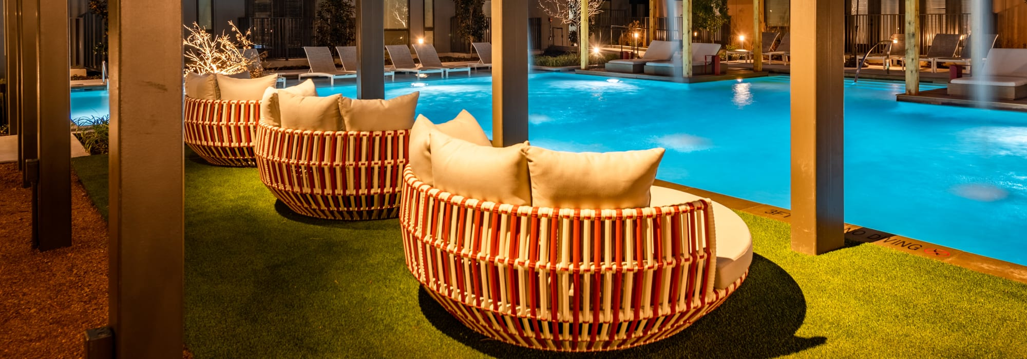 Resort-style swimming pool with shaded lounge seating nearby at The Langford in Dallas, Texas