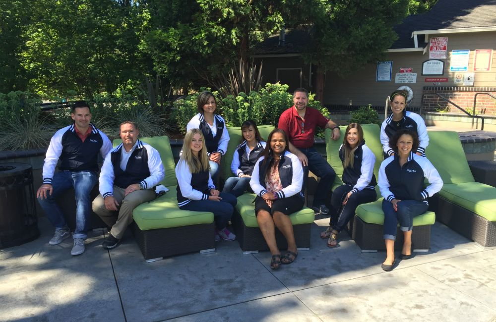 One of our community teams posing for a photo at American Property Management in Bellevue, Washington