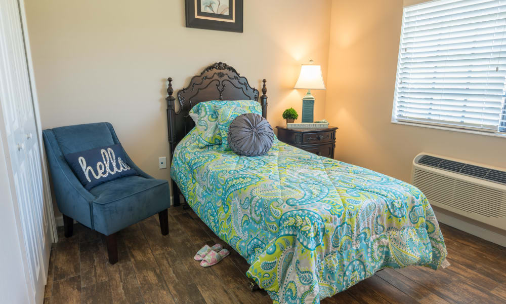 Resident bedroom with a side table at Inspired Living Ivy Ridge in St Petersburg, Florida