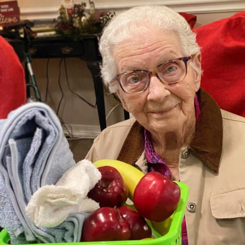 A resident sitting with a basket full of gifts at Canoe Brook Assisted Living in Ardmore, Oklahoma