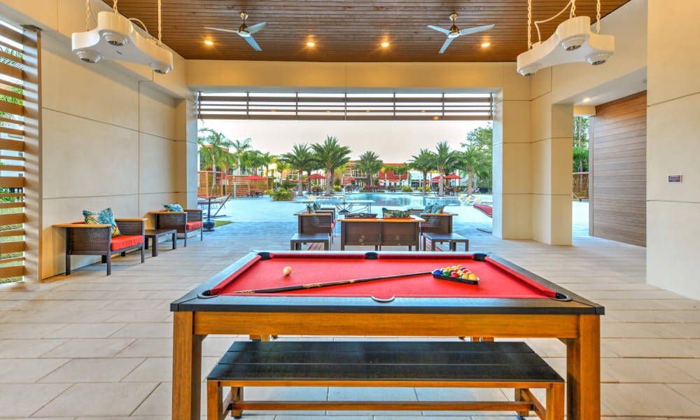 Open-air clubhouse lounge with a billiards table and more at Luxor Club in Jacksonville, Florida