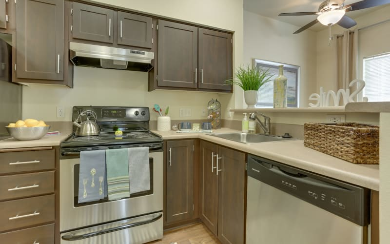 Recently renovated kitchen with brown cabinets and stainless steel appliances at The Landings at Morrison Apartments in Gresham, Oregon