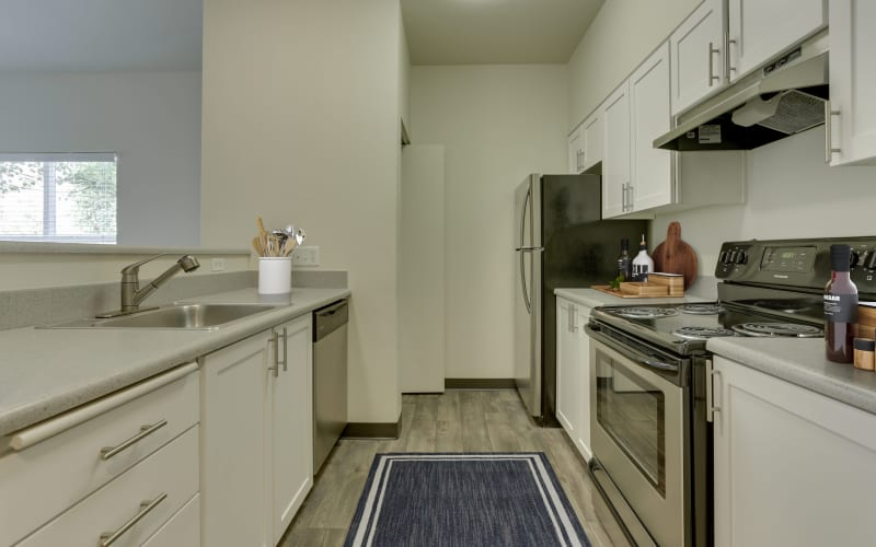 A bright and clean kitchen with white cabinets at The Landings at Morrison Apartments in Gresham, Oregon