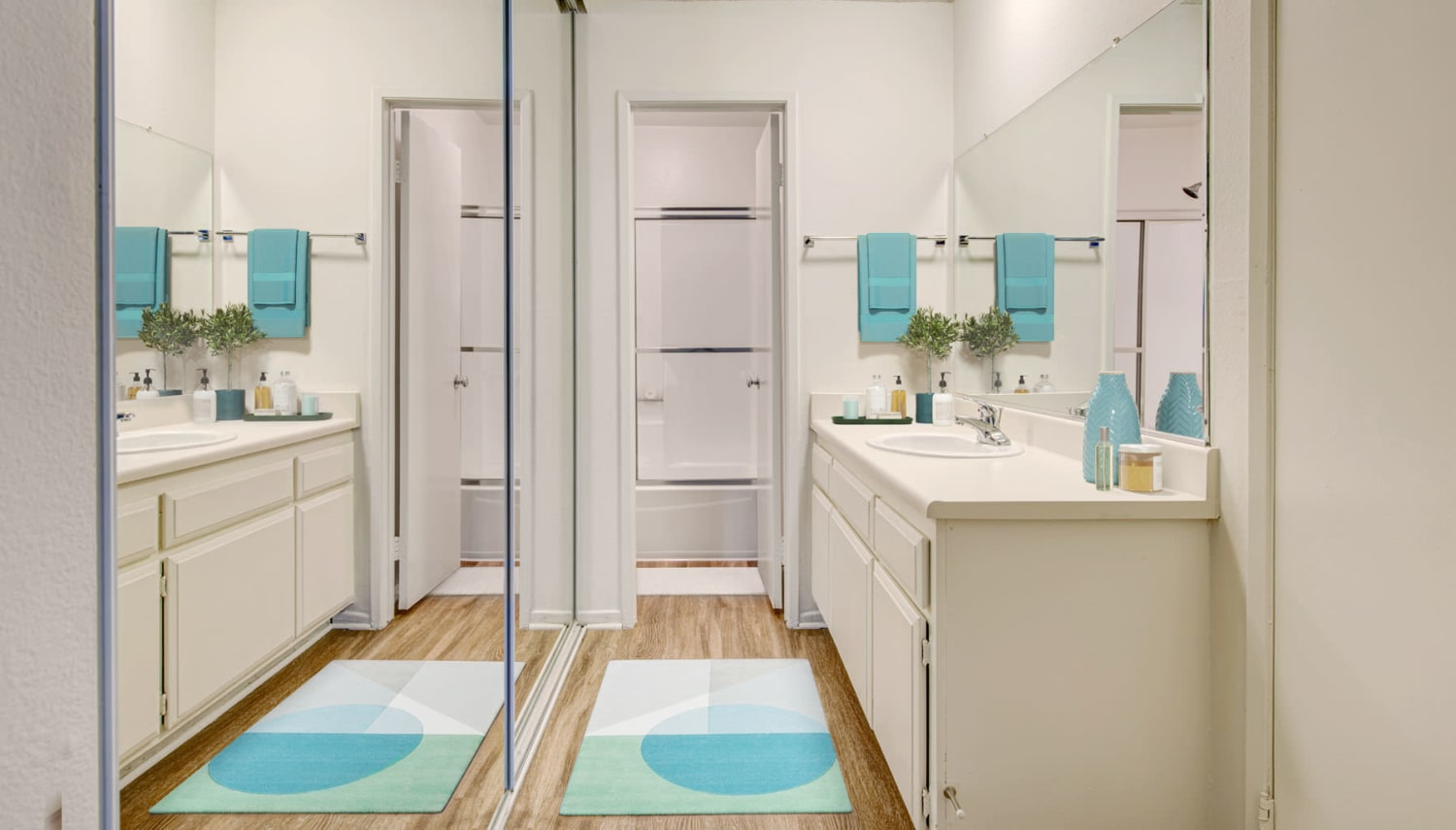 Bathroom with mirrored closet doors in a model apartment at Village Pointe in Northridge, California