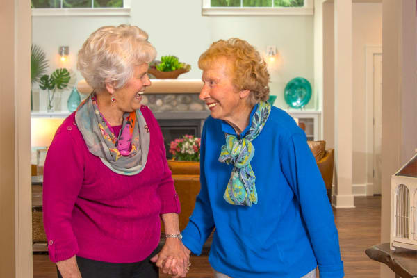 Two resident friends holding hands at Carefield Living.