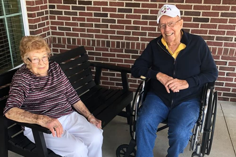 Residents enjoying the beautiful weather outside in the Courtyard at The Meadows of Ottawa in Ottawa, Ohio