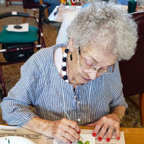 A happy resident painting at Canoe Brook Assisted Living & Memory Care in Catoosa, Oklahoma