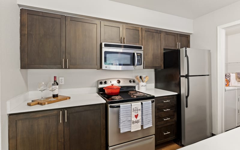Renovated brown kitchen with quartz counters at HighGrove Apartments in Everett, Washington