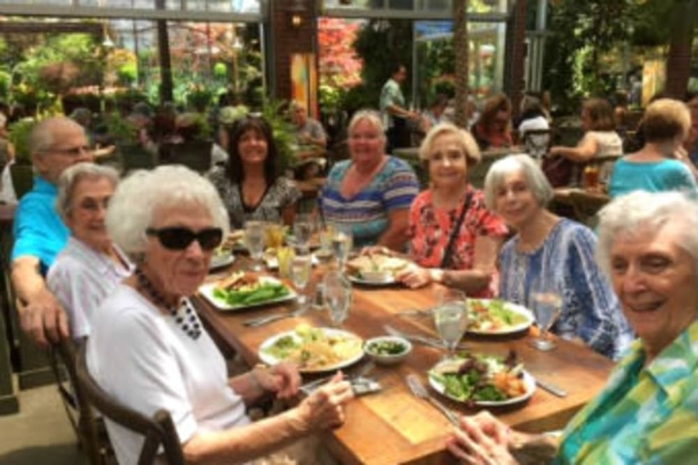 Happy friends eating lunch out and about  at Hilltop Commons Senior Living in Grass Valley, California