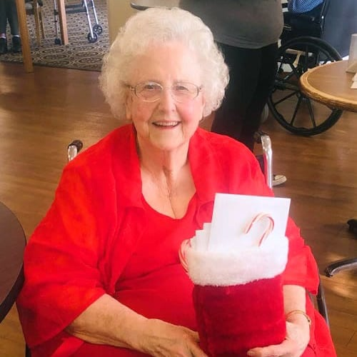 A resident holding a stocking full of small gifts at Ashbrook Village in Duncan, Oklahoma