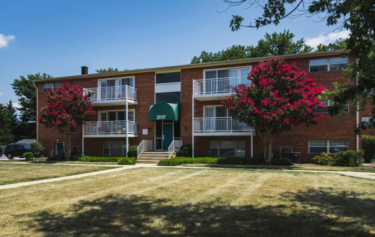 Exterior view of resident building and mature trees at Westgate Apartments & Townhomes in Manassas, Virginia