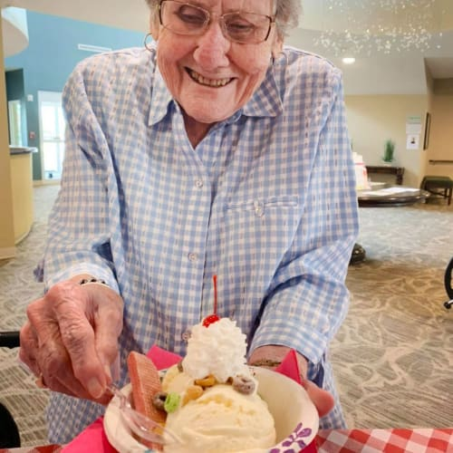 Resident with a large ice cream sundae at The Oxford Grand Assisted Living & Memory Care in McKinney, Texas