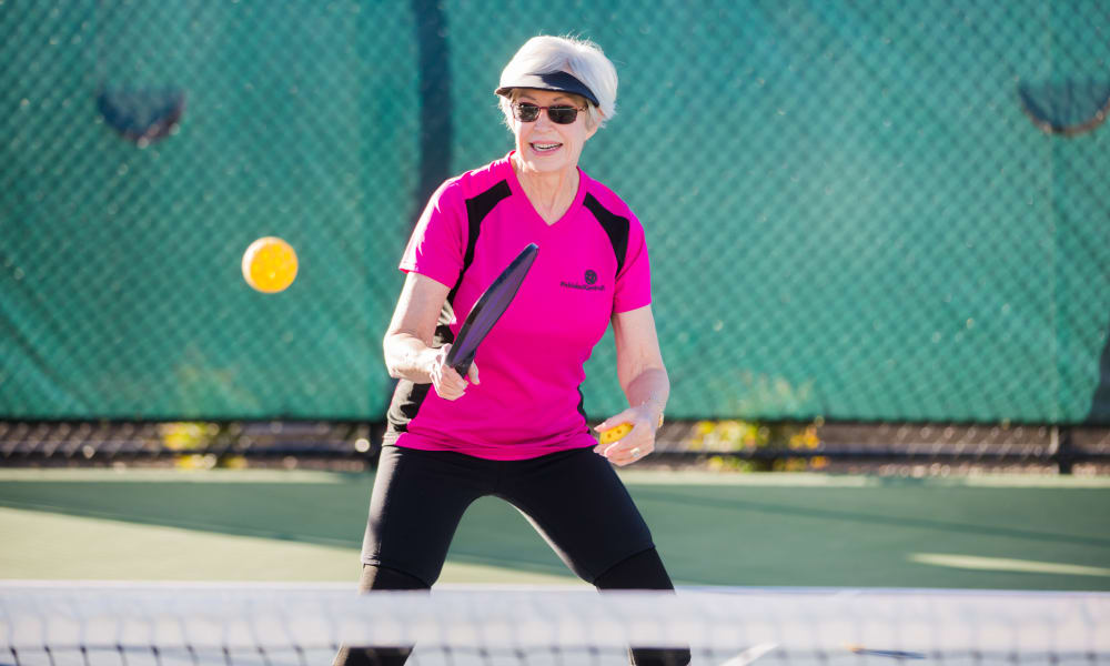 A resident from Touchmark in the West Hills in Portland, Oregon playing tennis