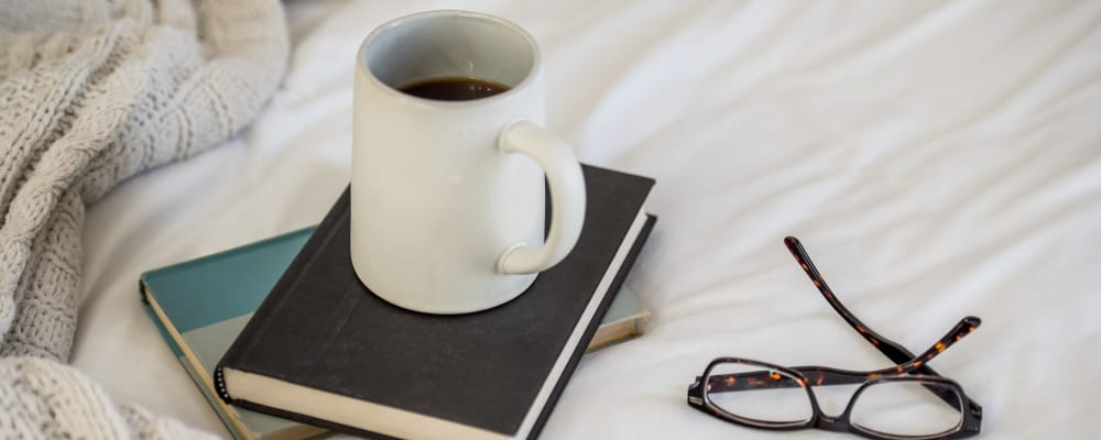 Books, coffee mug, and glasses resting on a bed at The Springs at Lancaster Village in Salem, Oregon