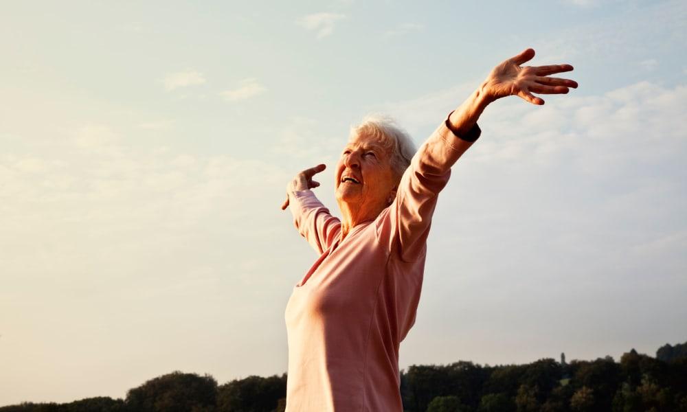 Senior woman raising her hands at The Phoenix at Estero in Estero, Florida