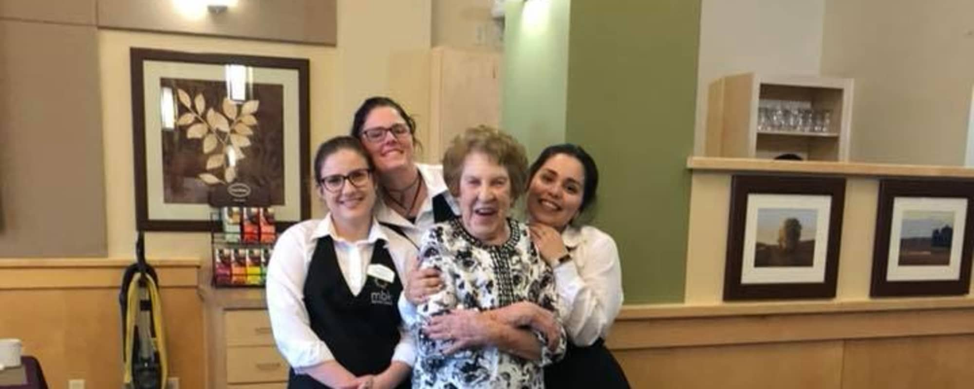Waitstaff hugging happy senior at Island House Assisted Living in Mercer Island, Washington