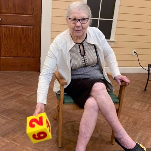 A resident playing a game with giant dice at Oxford Glen Memory Care at Owasso in Owasso, Oklahoma