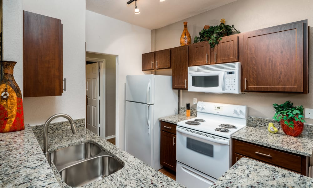 Bright kitchen with granite countertops and white appliances at Lakeview at Parkside in Farmers Branch, Texas