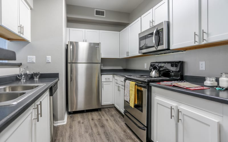 Renovated kitchen with white cabinets at Promenade at Hunter's Glen Apartments in Thornton, Colorado