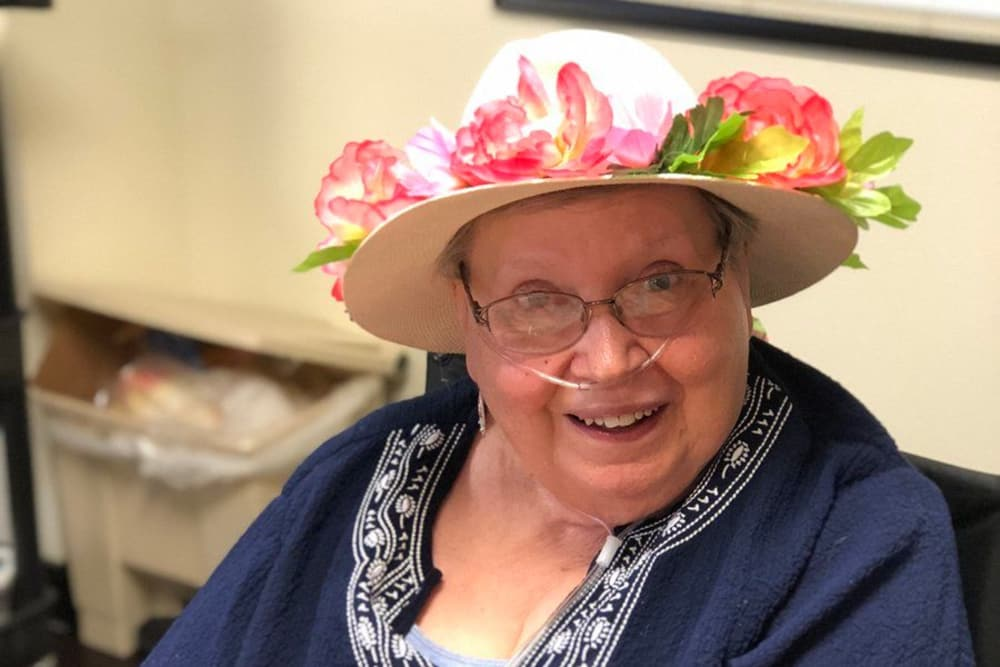 A resident with tropical flowers on her hat at River Terrace Health Campus in Madison, Indiana