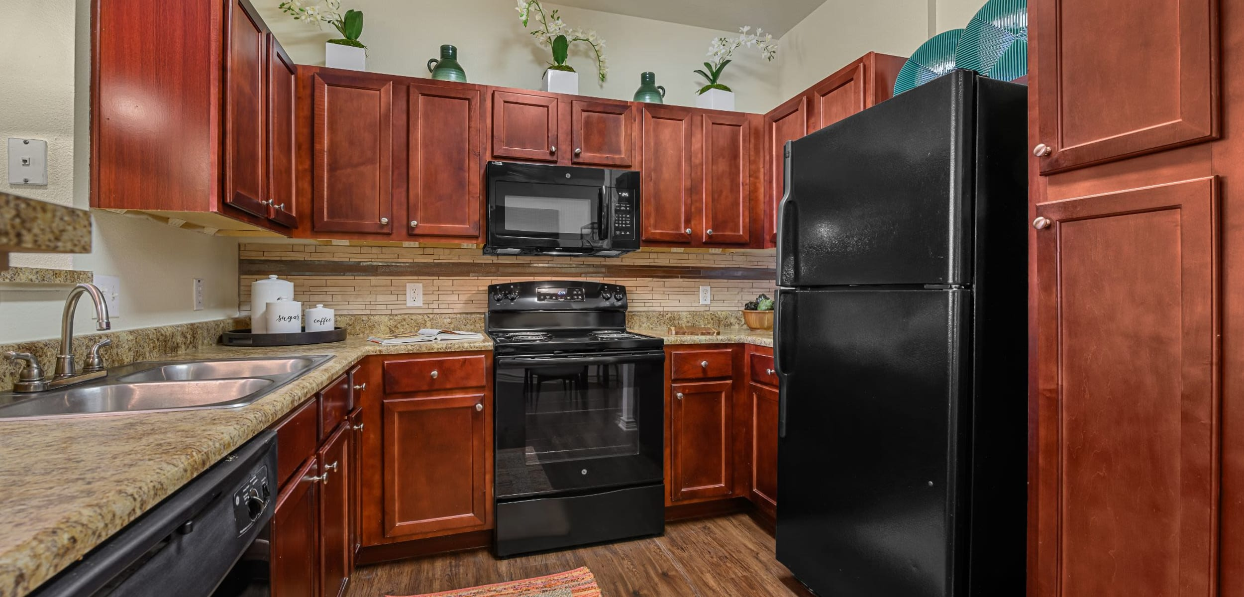 Modern kitchen with black appliances at Marquis Lakeline Station in Austin, Texas