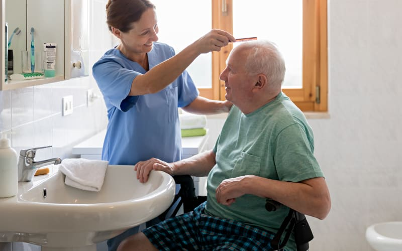 Caregiver combing a resident's hair at Chandler's Square Retirement Community in Anacortes, Washington
