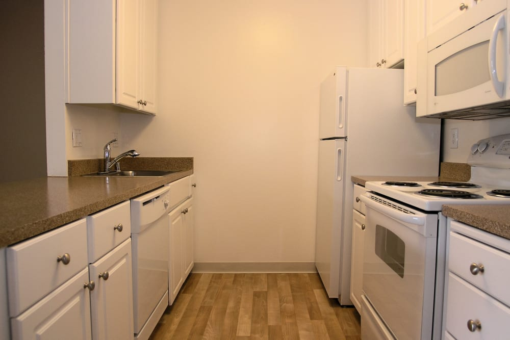 Kitchen with white appliances at Ballena Village Apartment Homes in Alameda, California