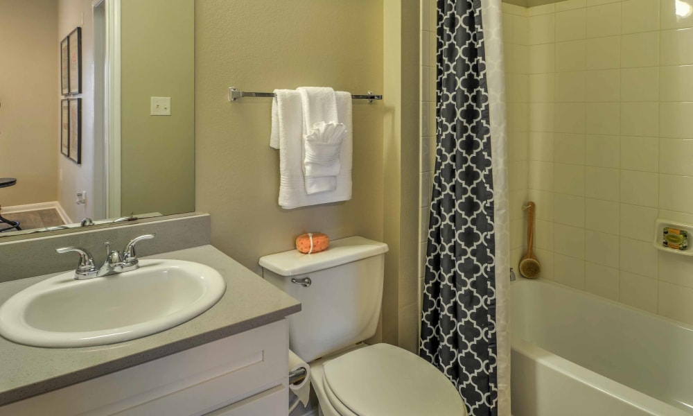 A bathroom and shower in an apartment at The Atlantic Station in Fort Worth, Texas