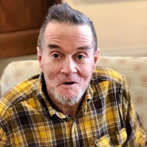 Resident wearing a yellow flannel at Oxford Glen Memory Care at Carrollton in Carrollton, Texas