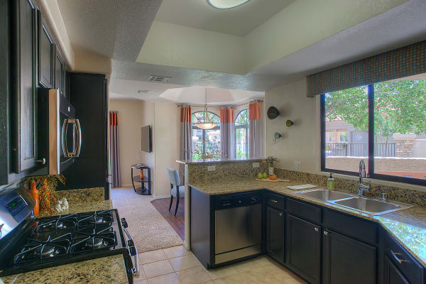 Modern kitchen with granite countertops in apartment home at San Pedregal in Phoenix, Arizona