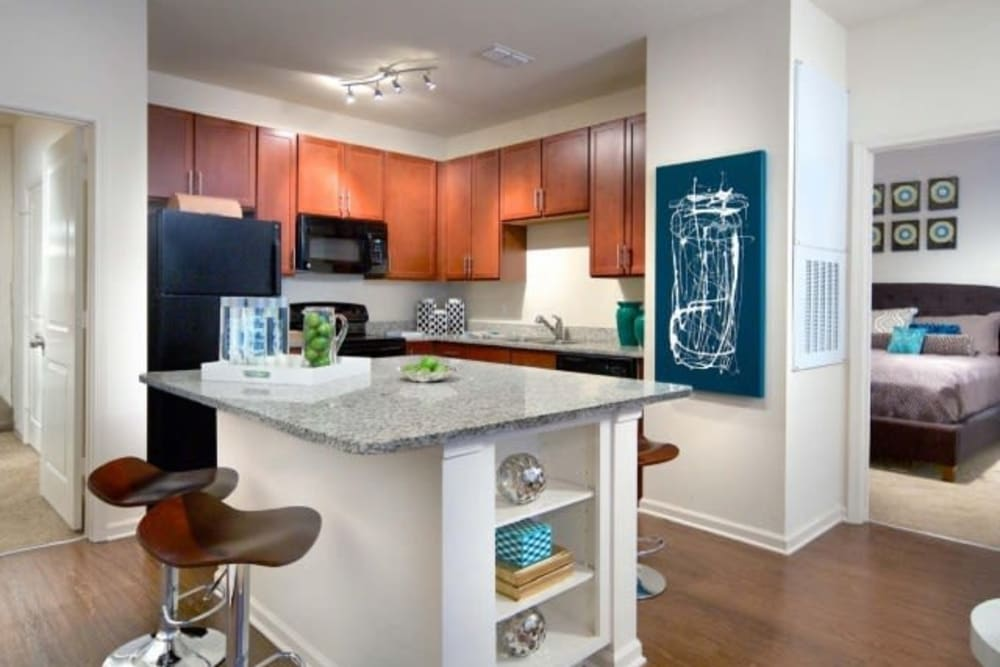 Modern kitchen with cherry wood cabinetry and an island in a model home at The Hawthorne in Jacksonville, Florida