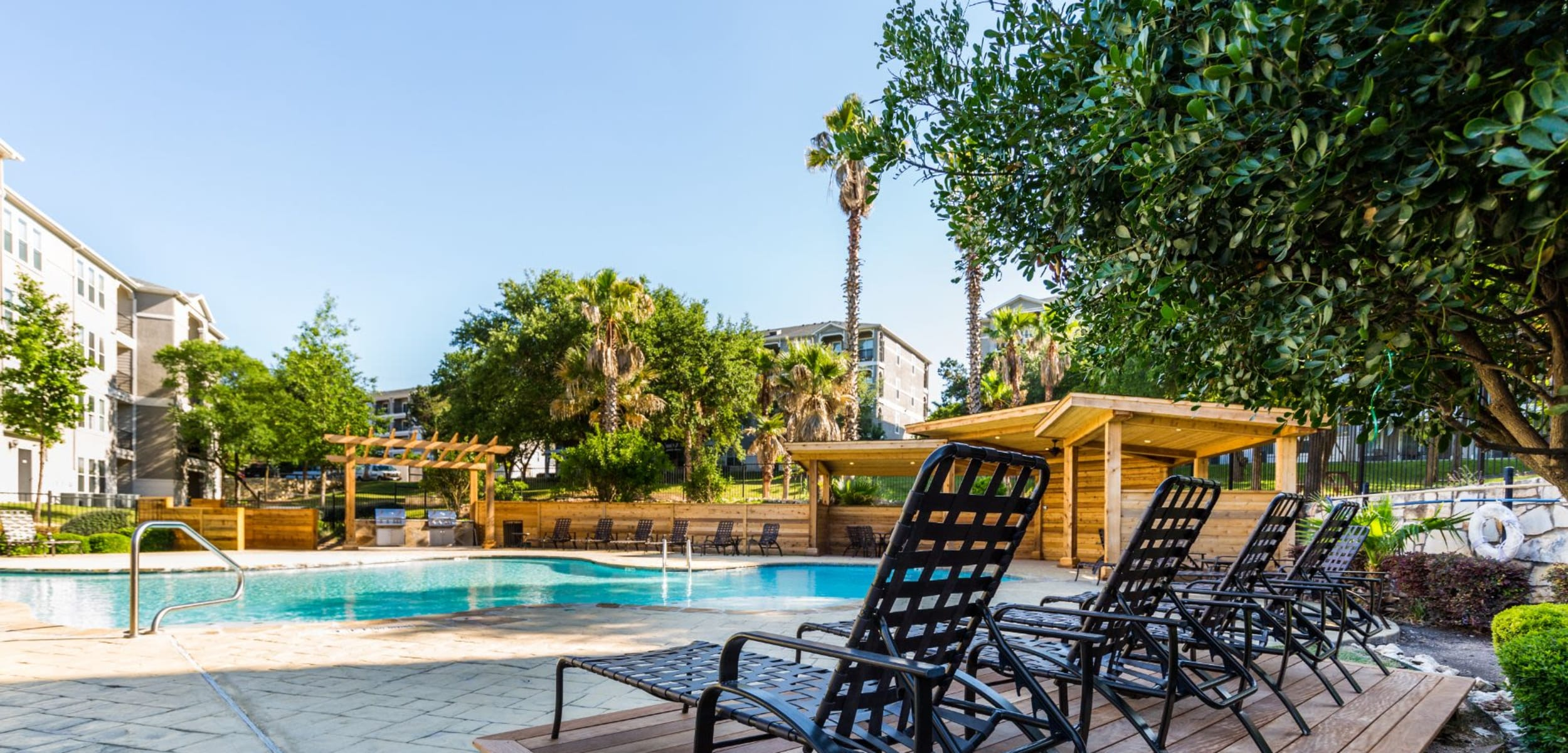 Swimming pool with sun chairs at Marquis at Crown Ridge in San Antonio, Texas