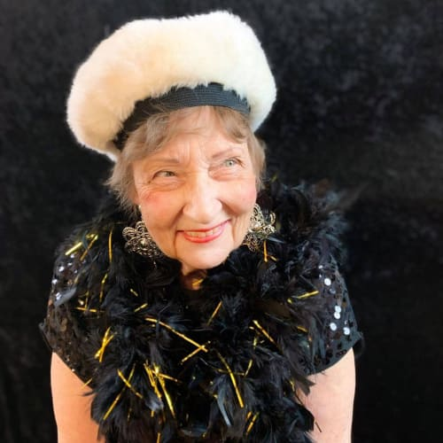 A smiling resident dressed up for an event at Oxford Glen Memory Care at Owasso in Owasso, Oklahoma