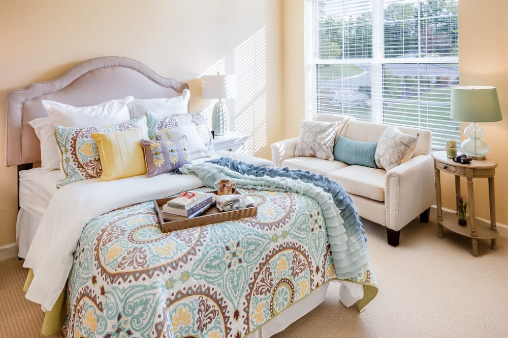 A bedroom with large windows at Anthology of Overland Park in Overland Park, Kansas.